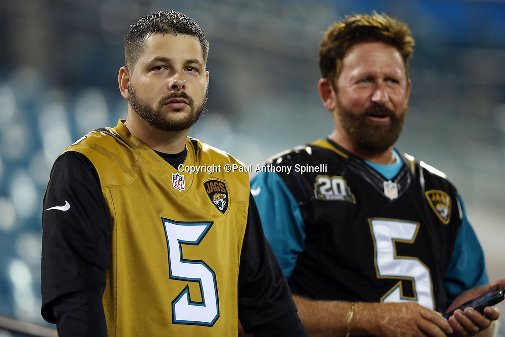"""A pair of Jacksonville Jaguars fans wear an old and a new """"color rush"""" jersey before the Jacksonville Jaguars 2015 week 11 regular season NFL football game against the Tennessee Titans on Thursday, Nov. 19, 2015 in Jacksonville, Fla. The Jaguars won the game 19-13. (©Paul Anthony Spinelli)"""