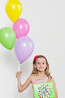 Portrait of a happy girl with party balloons and gift over colored background