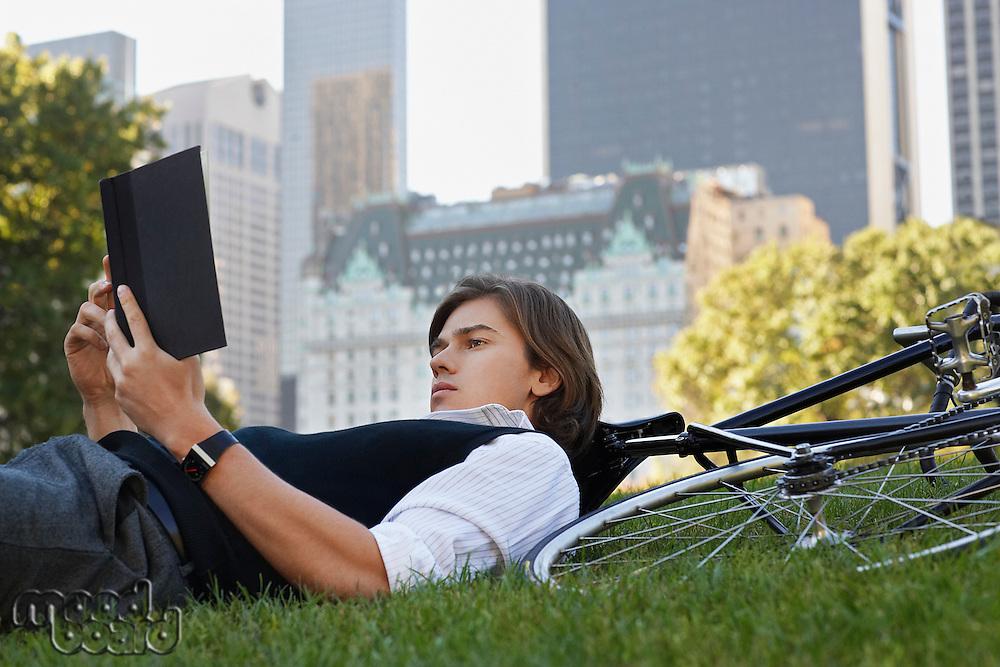 Man lying on lawn reading book