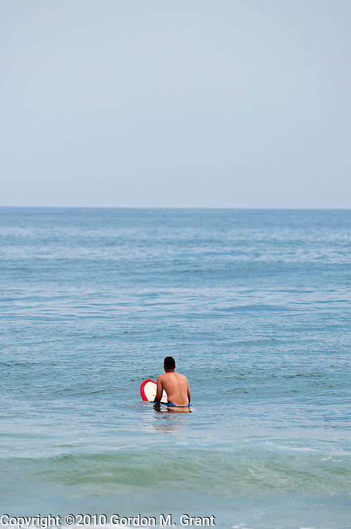 Amagansett, NY - 6/22/10 -   A surfer waits for the perfect wave in the Atlantic Ocean in Amagansett, NY June 22, 2010.     (Photo by Gordon M. Grant)