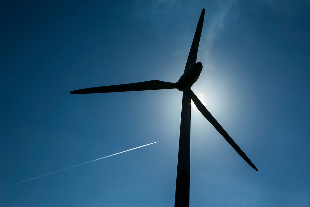 A plane and contrail flying over St Briavels wind turbine, at Great Dunkilns Farm, St. Briavels, Lydney, Gloucestershire.