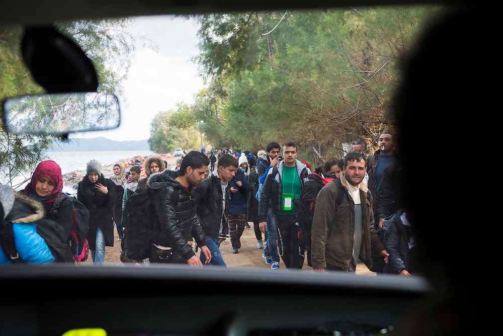 A car driving along the northern coast of the Greek island of Lesbos, between the town of Molyvos and village of Skala Skamnias, slows before a crowd of migrants walking along the road shortly after arriving by boat from Turkey.