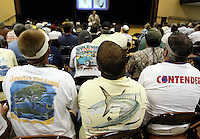 "Men wearing shirts with a pictures of fish on the back listen to a BP contractor lead a class in BP's ""Vessel of Opportunity"" program for commercial fishermen and boat owners in Biloxi, Mississippi May 5, 2010.  The program trains boat operators in treating the oil spill still offshore. REUTERS/Rick Wilking (UNITED STATES)"