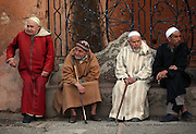 A group of old men sit in the town square people-watching in Chefchaouen, Morocco.
