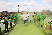 Local Athens volunteers prepare to blast oncoming runners with green corn starch powder before they cross the finish line. Photos by Elizabeth Held
