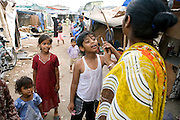 Azharuddin Ismail, 10, the child actor playing the role of 'young Salim', the brother of Jamal, protagonist of Slumdog Millionaire, the famous movie winner of 8 Oscar Academy Awards in December 2008, is having a small discussion with his mother over his mobile phone in the slum where he still lives with his family next to the train station of Bandra (East), Mumbai, India. Various promises were made to lift the two young actors (Azharuddin Ismail and Rubina Ali) from poverty and slum-life but as of the end of May 2009 anything is yet to happen. Rubina's house was recently demolished with no notice as it lay on land owned by the Maharashtra train authorities and she is now permanently living with her uncle's family in a home a stone-throw away in the same slum. Azharuddin's home too was demolished in the past two weeks, as it happens every year in his case, because the concrete walls were preventing local authorities to clear a drain passing right behind it. As usual, his father is looking into restoring the walls as soon as the work on the drain has been completed.