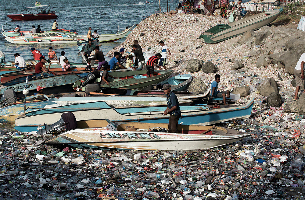 Waterfront scene of people in taxi boats in an ocean full of plastic garbage in Semporna, Borneo, Malaysia