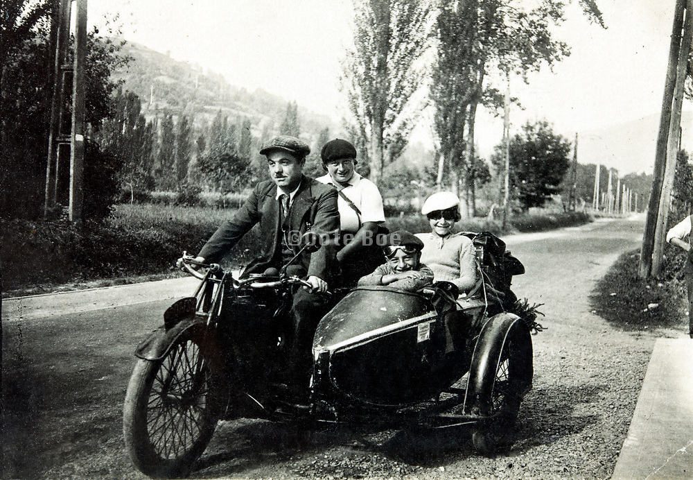 family with 2 children traveling on a motorcycle and sidecar 1930s France