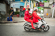 """10 DECEMBER 2012 - BANGKOK, THAILAND:  A Red Shirt protestor wearing a hat modeled after Bangkok's Democracy Monument on a motorcycle on Petchaburi Rd in Bangkok near the offices of the ruling Pheu Thai party Monday to call for constitutional reform. The Thai government announced on Monday, which is Constitution Day in Thailand, that will speed up its campaign to write a new charter. December 10 marks passage of the first permanent constitution in 1932 and Thailand's transition from an absolute monarchy to a constitutional monarchy. Several thousand """"Red Shirts,"""" supporters of ousted and exiled Prime Minister Thaksin Shinawatra, motorcaded through the city, stopping at government offices and the offices of the Pheu Thai ruling party to present demands for a new charter.        PHOTO BY JACK KURTZ"""