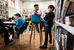© Licensed to London News Pictures. 01/04/2016. London, UK. Two boys chat as they take part in the occupation of the Carnegie Library in Herne Hill, south London, in an effort to prevent its closure. Lambeth Council had planned to close the library last night (31st March) in order to turn it into a 'healthy living centre'. Photo credit : Rob Pinney/LNP