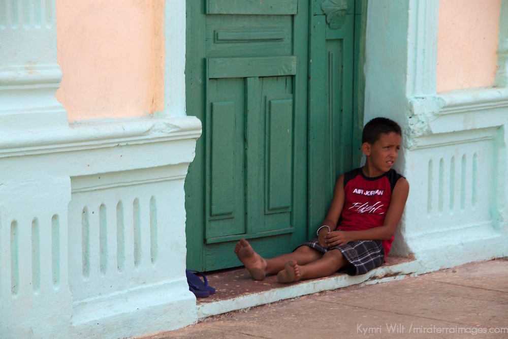 Central America, Cuba, Remedios. Cuban boy relaxing in doorway.