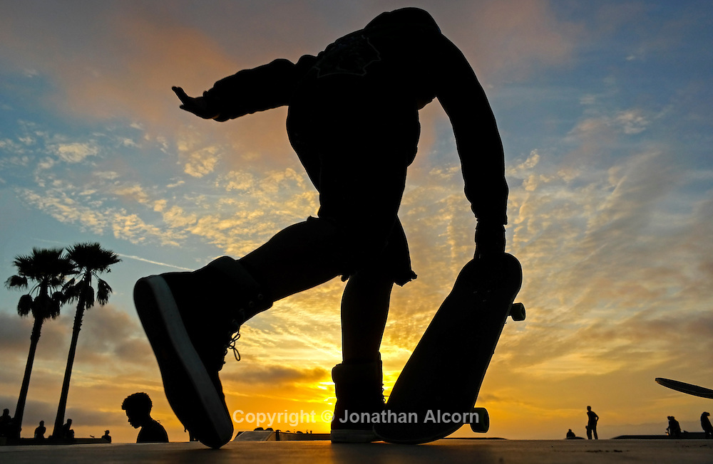 A skateboarder takes off at the Venice Skate Park as the sun sets into the Pacific.