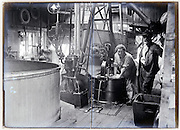 woman and man working in an early 1900s industrial sized laundrymat