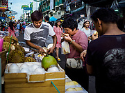"24 JULY 2018 - BANGKOK, THAILAND: Tourists buy durian from a street vender on Khao San Road, in Bangkok. Khao San Road is Bangkok's original ""Backpacker Ghetto"" and is still a popular hub for travelers, with an active night market and many street food stalls. The Bangkok municipal government plans to shut down the street market by early August because city officials say the venders, who set up on sidewalks and public streets, pose a threat to public safety and could impede emergency vehicles. It's the latest in a series of night markets the city has closed.    PHOTO BY JACK KURTZ"