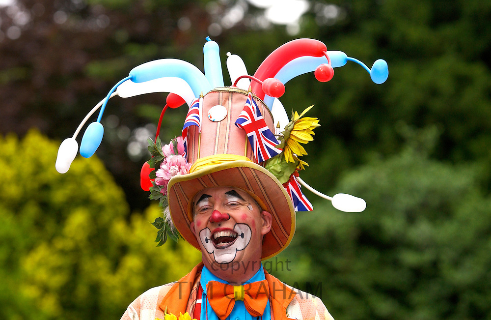 A clown laughing during a community picnic where local groups are providing musical and dance entertainment to celebrate the ethnic diversity of West London at Gunnersbury Park