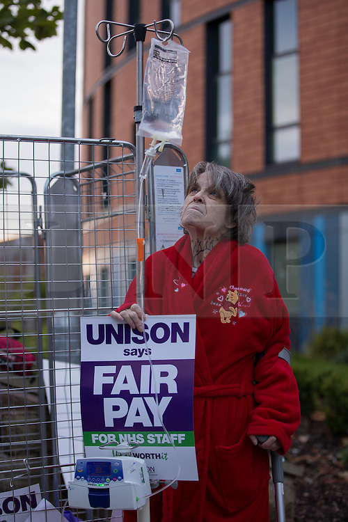"""© Licensed to London News Pictures . 13/10/2014 . Salford , UK . A patient in a dressing gown carrying a crutch and a drip , joins the protest outside the hospital . NHS staff picket outside the Salford Royal (formerly """" Hope """") Hospital in Greater Manchester as nurses, midwives and ambulance staff stage a four hour strike over pay .  Photo credit : Joel Goodman/LNP"""
