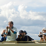 Japanese tourists taking pictures from roof of safari vehicle. Masai Mara, Kenya