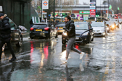 © Licensed to London News Pictures. 20/12/12/019. London, UK. A man is seen jumping through a flood on Green Lanes, Harringay in North London, caused by overnight heavy rainfall and a pipe burst.  Photo credit: Dinendra Haria/LNP
