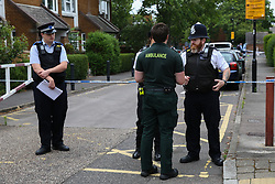 © Licensed to London News Pictures. 04/07/2020. London, UK. A paramedic speaks with police officers on Roman Way, Islington in north London as police launch a murder investigation following fatal shooting. Police were called at at 3.20pm to Roman Way, following reports of shots fired.  Officers attended with LAS and found a man, believed to be aged in his early 20s, suffering from gunshot injuries. Despite their best efforts, he was pronounced dead at the scene. Photo credit: Dinendra Haria/LNP