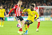 Arsenal midfielder Bukayo Saka (77) and Sheffield United forward Oli McBurnie (9) battle for the ball during the Premier League match between Sheffield United and Arsenal at Bramall Lane, Sheffield, England on 21 October 2019.
