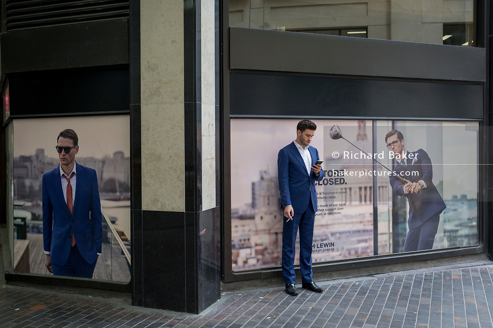 A young businessman checks messages with a cigarette by posters featuring men in matching blue suits in the City of London, the capital's financial district aka The Square Mile, on 29th August 2018, in London, England.