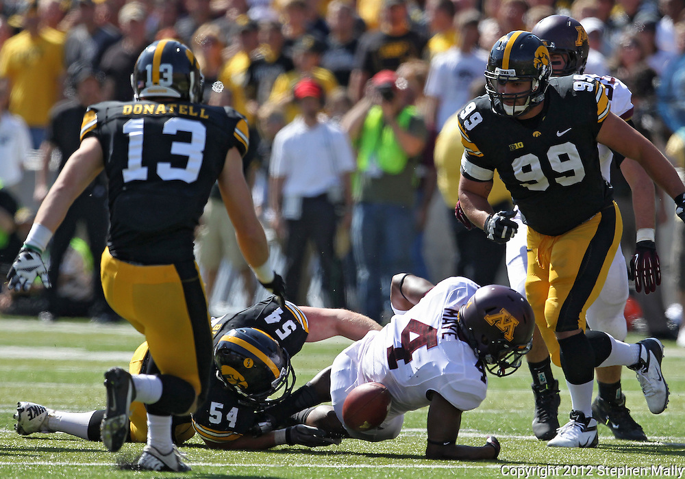 September 29 2012: Minnesota Golden Gophers running back KJ Maye (4) fumbles the ball as he is hit by Iowa Hawkeyes defensive lineman Steve Bigach (54) during the third quarter of the NCAA football game between the Minnesota Golden Gophers and the Iowa Hawkeyes at Kinnick Stadium in Iowa City, Iowa on Saturday September 29, 2012. Iowa defeated Minnesota 31-13 to claim the Floyd of Rosedale Trophy.