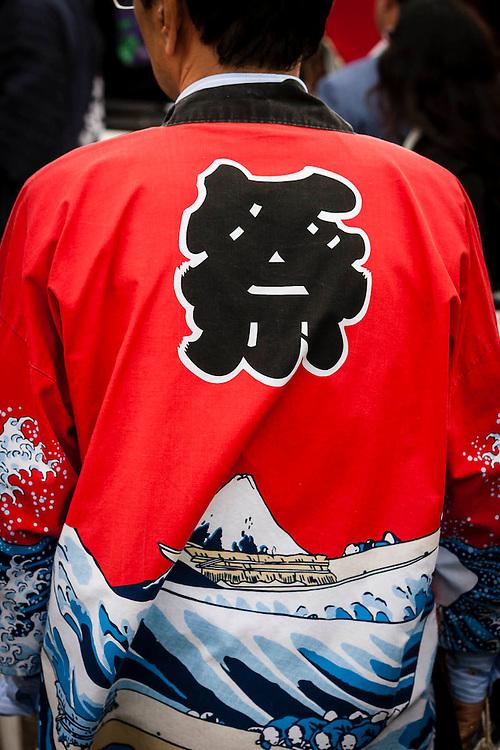 A man wears a red yukata with japanese kanji and motifs