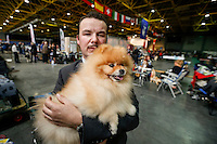 A man shows his Keeshond dog at the 50th Euro Dog Show in Kortrijk, Belgium, 16 November 2013.