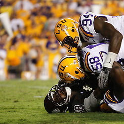 Sep 18, 2010; Baton Rouge, LA, USA;  LSU Tigers linebacker Tahj Jones (58) and defensive end Kendrick Adams (94) tackle Mississippi State Bulldogs running back Vick Ballard (28) during the second half at Tiger Stadium. The LSU Tigers defeated the Mississippi State Bulldogs 29-7. Mandatory Credit: Derick E. Hingle