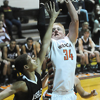 New Hanover's Brian Howell shoots over Ashley's Bryston Davis Friday December 19, 2014 at New Hanover High School in Wilmington, N.C. (Jason A. Frizzelle)