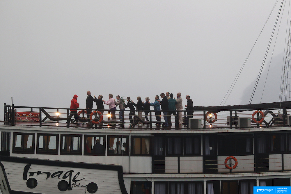An early morning Tai chi class on board a tourist Junks in Ha Long Bay, Vietnam. The bay consists of a dense cluster of 1,969 limestone monolithic islands. Ha Long Bay, is a UNESCO World Heritage Site, and a popular tourist destination. Ha Long, Bay, Vietnam. 11th March 2012. Photo Tim Clayton