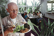 Biosphere 2 Project undertaken by Space Biosphere Ventures, a private ecological research firm funded by Edward P. Bass of Texas.  Roy Walford, former pathologist at UCLA and one of the eight inhabitants of the Biosphere, seen inside Biosphere 2 with his lunch (all food grown in the Biosphere). Walford authored a book titled The Anti-Aging Plan. He died in 2004 at age 79 of ALS. Walford had been involved in the Project since 1983, and set up the Biosphere's medical centre.  Biosphere 2 was a privately funded experiment, designed to investigate the way in which humans interact with a small self-sufficient ecological environment, and to look at possibilities for future planetary colonization.  MODEL RELEASED 1992