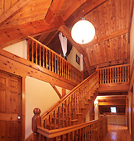 Timber frame cottage style Canadian country house interior with a wooden staircase leading to the loft, Muskoka, Ontario, Canada