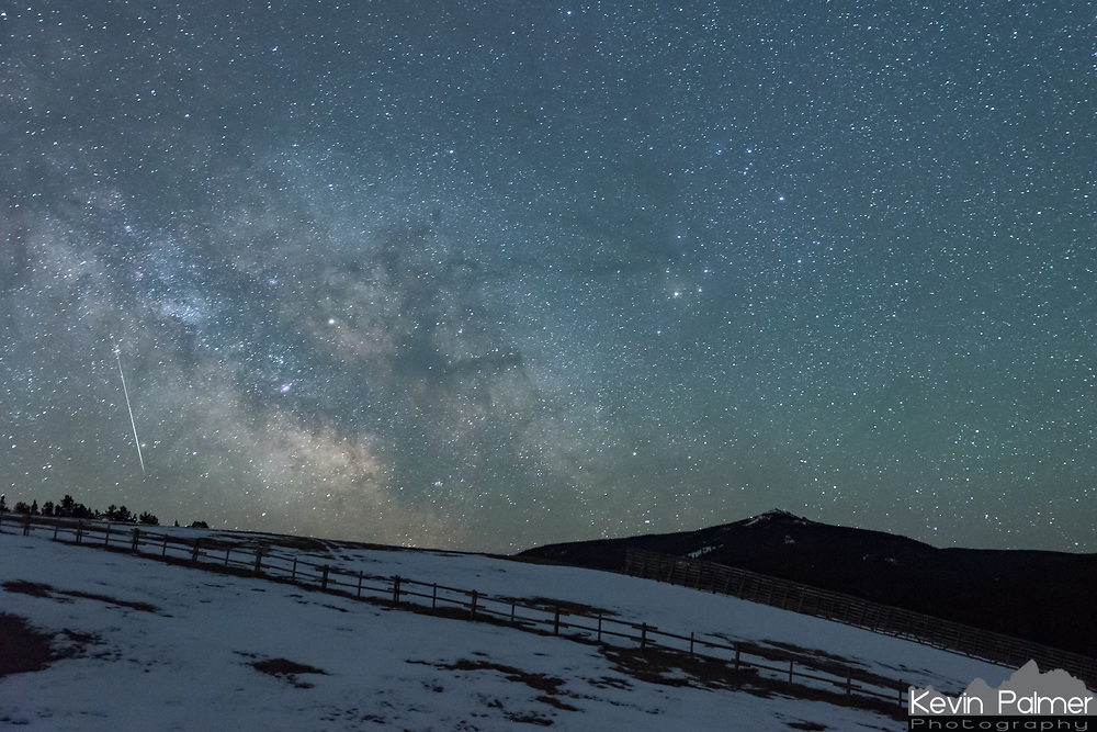The milky way galaxy rises above Black Mountain while a Lyrid meteor pierces the sky.