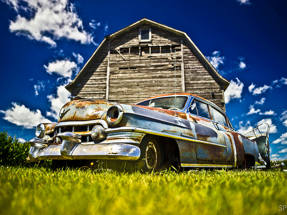 A rusted Cadillac sits parked in front of a barn off the Lincoln Highway in Western Illinois. <br /> <br /> /// ADDITIONAL INFORMATION: 7/24/11 - travel.Lincoln.East.0929  - STUART PALLEY, ORANGE COUNTY REGISTER - Lincoln Highway July 2013.