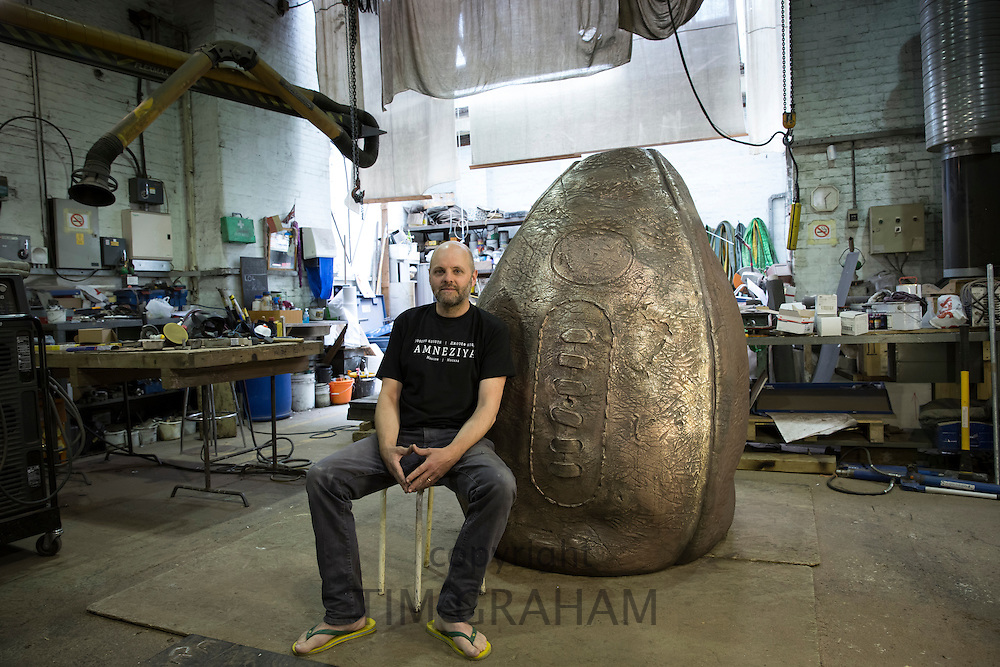Sculptor Gavin Turk with his rugby ball sculpture 'Birth of the Egg Ball' at its bronze forged stage of creation for Rugby School, birthplace of the sport