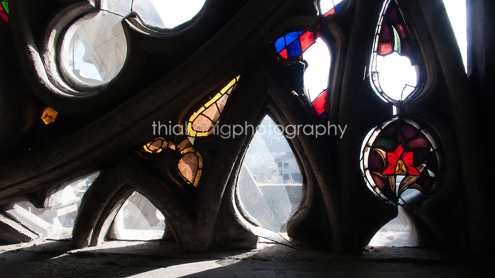 Looking out to the city of Quito, Ecuador through odd shaped windows and broken stained glass.
