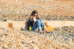 © Licensed to London News Pictures.08/04/2020. Brighton, UK. Members of the public enjoy the warmer weather by relaxing on the beach and taking a walk on the Brighton and Hove promenade. Photo credit: Hugo Michiels/LNP