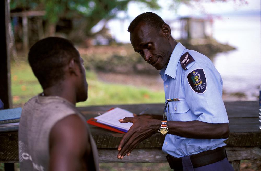 RSIP Sgt. AllinsonTiazy discusses allegations of threatening behaviour with suspect Dick Dani at Ughele Village, Rendova Island - The Solomon Islands