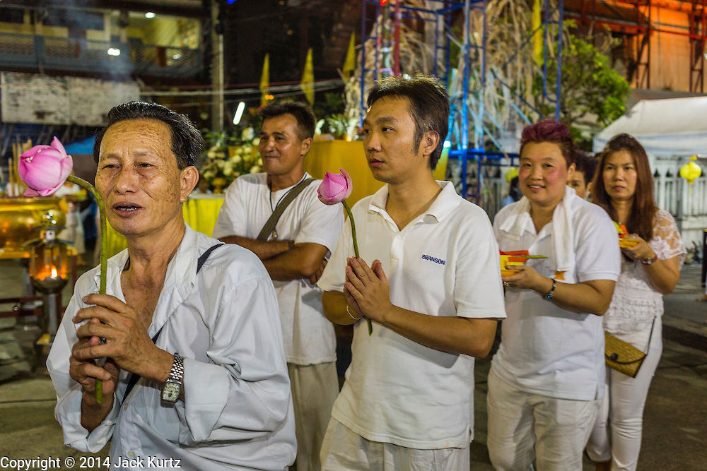 01 OCTOBER 2014 - BANGKOK, THAILAND: A procession before the firewalking at Wat Yannawa (also spelled Yan Nawa) during the Vegetarian Festival in Bangkok. The Vegetarian Festival is celebrated throughout Thailand. It is the Thai version of the The Nine Emperor Gods Festival, a nine-day Taoist celebration beginning on the eve of 9th lunar month of the Chinese calendar. During a period of nine days, those who are participating in the festival dress all in white and abstain from eating meat, poultry, seafood, and dairy products. Vendors and proprietors of restaurants indicate that vegetarian food is for sale by putting a yellow flag out with Thai characters for meatless written on it in red.     PHOTO BY JACK KURTZ