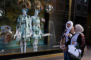 Two Muslim women walk past a display of eccentric mannequins in diving masks and snorkels, outside a central London branch of Ted Baker.