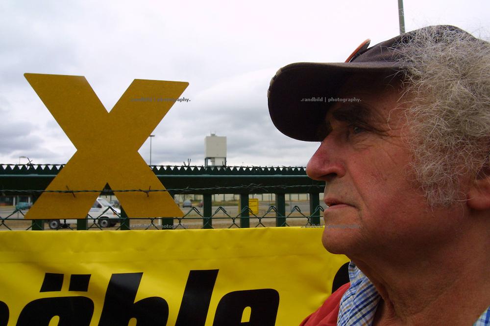 Egon Maierhofer (Pastor i.R.) vor dem Zaun des Erkundungsbergwerkes in Gorleben. Ein aufgestecktes Widerstand-X steckt im Stacheldraht. Im Hintergrung der Turm von Schacht 1 des potentiellen Endlagers für Atommüll.