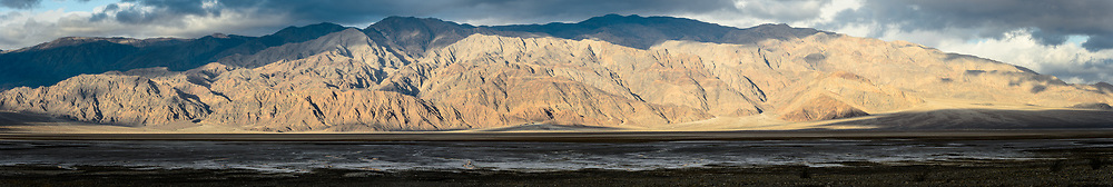 The Panamint Range is bathed in morning light at sunrise above Cottonball Basin in Death Valley National Park. Salt formations in the basin are the result of mineral rich water evaporating until only the salts remain. It is a repeating process, which over thousands of years, layers of salt into polygon-shaped crust. The Death Valley saltpan is one of the largest protected saltpans in North America.<br /> <br /> Death Valley National Park, located in eastern California near the border with Nevada is one of the hottest spots on earth, holding the hottest recorded air temperature of 134 &deg;F. The Park also is location of the lowest spot in North America, 282 feet below sea level at the vast salt flats at Badwater Basin. At 3.4 million acres, the park is the largest national park in the contiguous United States. Death Valley National Park sits between the Panamint Range on the west  and Amargosa Range on the east.<br /> <br /> EDITORS NOTE: This image is a panorama composite made of several overlapping images.