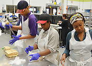 Second year H.E.A.R.T. students Trevor and LaRonda package cut pieces of pita bread in Keegan Kitchen at the Houston Food Bank.