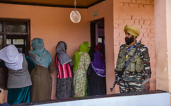 October 10, 2018 - Srinagar, Jammu and Kashmir, India - Kashmiri women stand in queue to to cast their votes as an Indian paramilitary trooper stands guard during the second phase of municipal polls. Poor voter turnout marked the second phase of municipal elections in Kashmir amid a partial shutdown and heavy deployment of government forces across the region. (Credit Image: © Yawar Nazir/ZUMA Wire)