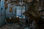 Donetsk, Ukraine - August 6, 2014: Valentina Romanova, 72, aunt of unseen Irina Motova, 57, walks through Motova's destroyed bedroom after her house being hit by shelling on the outskirts of Donetsk. CREDIT: Photo by Mauricio Lima for The New York Times