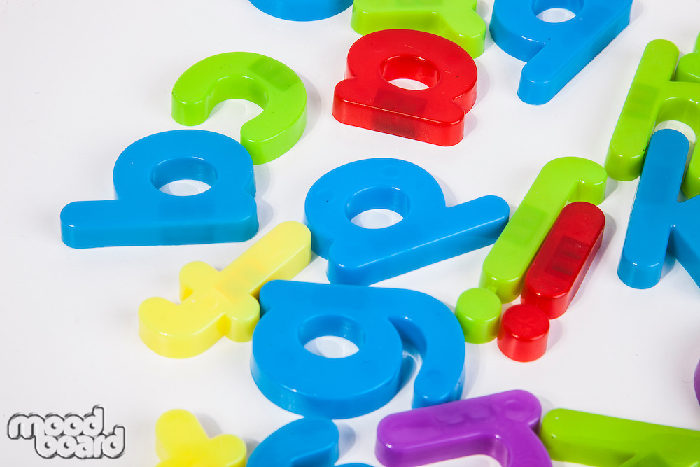 Close-up view of alphabet magnets scattered over white background