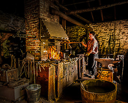 Don Mackay, blacksmith, working the bellows in a smiddy on the Rideau Canal