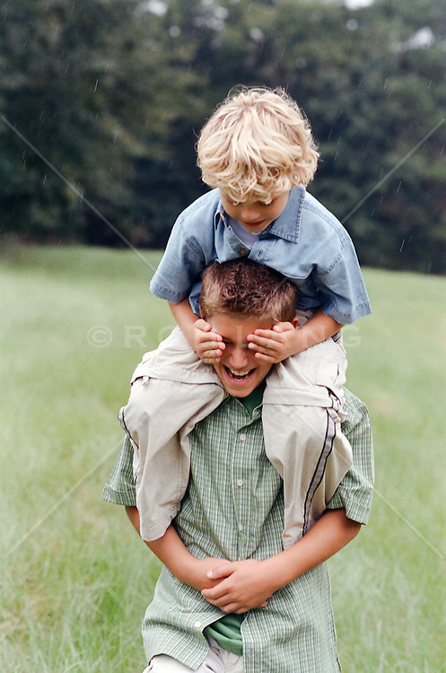 two boys enjoying a piggy back ride in the country