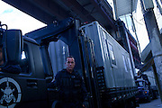 Police officers of special platoon BOPE drive a truck with a container that will host a police station as they  occupy the Caju slum complex during a cojoint operation to install a Pacifying Police Unit (UPP) in Rio de Janeiro, Brazil, Sunday, March 3, 2013. The action is part of a program aiming to drive armed drug gangs out of Rio's slums.